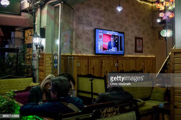 People sit in a cafe while coverage of the referendum results play on a tv on April 16 2017 in Istanbul Turkey According to unofficial results 5121%...