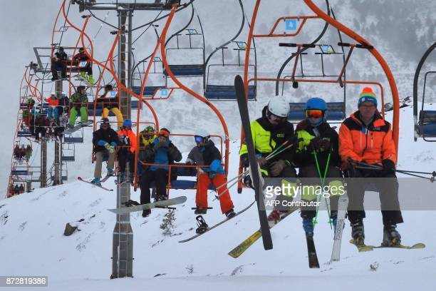 People sit in a chairlift in the French Pyrenean ski resort of PortePuymorens on November 11 on its first opening day / AFP PHOTO / RAYMOND ROIG