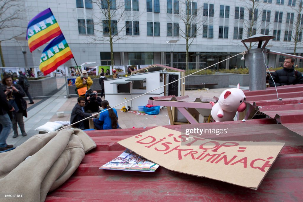 People sit in a fake Roma camp set up during a protest organised by Amnesty International against discrimination of Roma people in Europe, on April 8, 2013 in Brussels. AFP PHOTO/BELGA/ KRISTOF VAN ACCOM -Belgium Out-