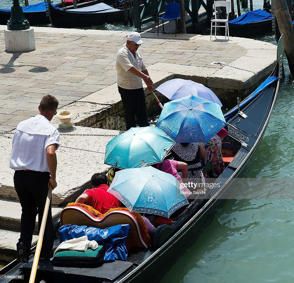 People sit in a Gondola under umbrellas on June 21, 2012 in Venice, Italy. An intense heatwave is sweeping across many regions in Italy, prompting the country's health ministry to issue a number of high level alerts.