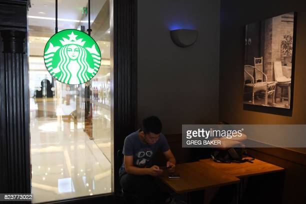 People sit in a Starbucks coffee shop in Beijing on July 28 2017 US coffee chain Starbucks has announced it will take full control of its mainland...