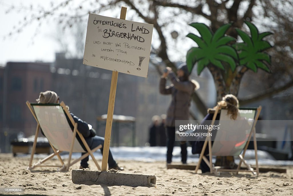 People sit in deck chairs of an urban beach waiting for US actor and singer David Hasselhoff (unseen) touring the East Side Gallery part of the remains of the former Wall in Berlin on March 17, 2013. The former Bay Watch star came to the German capital to lend his support to the movement for that want to preserve the 1,3km long stretch of the cold war symbol and keep the land along river Spree as public land.