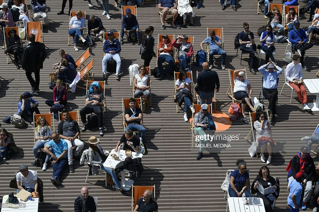 People sit in deckchairs in the sun in at the Roland Garros 2016 French Tennis Open in Paris on May 25, 2016. / AFP / MIGUEL