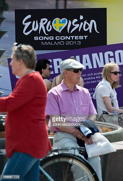 People sit in front of a Eurovision logo at a Eurovision public viewing area in downtown Malmo ahead of the finals of the 2013 Eurovision Song...