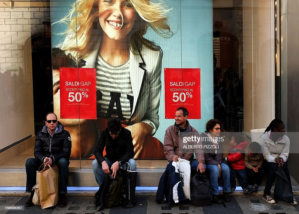 People sit in front of a shop advertising its sale, on January 5, 2013 during the first day of sales in Rome. AFP PHOTO / ALBERTO PIZZOLI