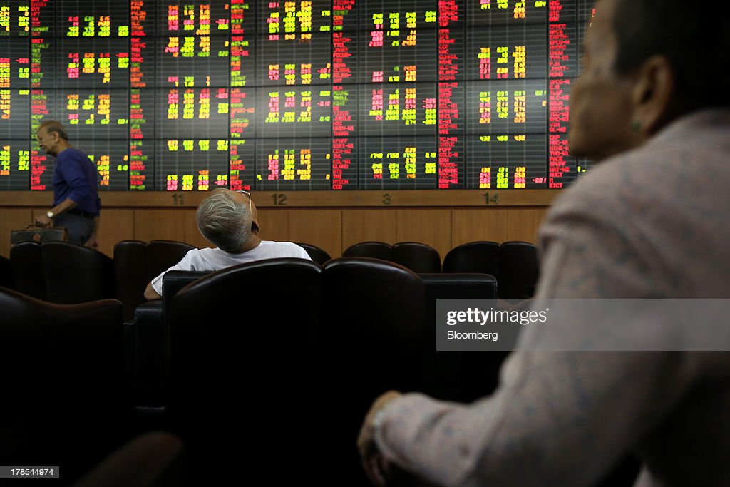 People sit in front of an electronic stock board at the Asia Plus Securities Pcl headquarters in Bangkok, Thailand, on Friday, Aug. 30, 2013. Stocks in Southeast Asia are tumbling at the fastest pace in 12 years relative to global equities, sending the regional benchmark index into a bear market as foreign investors cut holdings for a third month. Photographer: Dario Pignatelli/Bloomberg via Getty Images