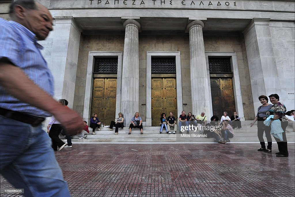 People sit in front of National Bank of Greece on September 15, 2011 in Greece. As Greece's position in the Eurozone remains uncertain, a cabinet meeting today discussed how the country may implement a new round of austerity measures in order to fend off default and to ensure they continue to receive rescue loans. The troubled country is in its third year of recession and unemployment has risen to 16.3% compared with 11.8% this time last year.