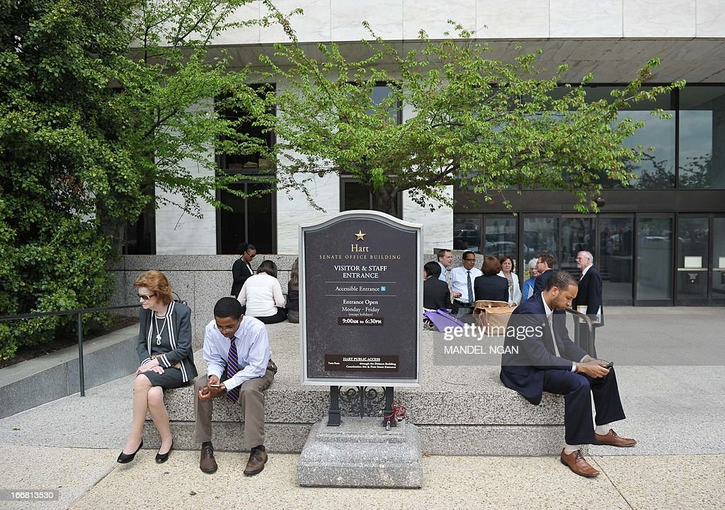 People sit in front of the Hart Senate Office Building after it was evacuated on April 17, 2013 on Capitol Hill in Washington, DC. US Capitol Police are investigating several suspicious packages that were delivered to the Hart and Russell Senate Office buildings. AFP PHOTO/Mandel NGAN