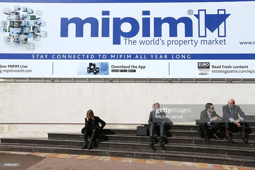 People sit in front of the Palais des Festivals on March 13, 2013 in Cannes, southeastern France, during the MIPIM, an international real estate show for professionals. The event takes place until March 15.