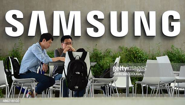 People sit in front the logo of South Korean electronics giant Samsung ahead of the opening of the 55th IFA on September 2 2015 in Berlin IFA one of...