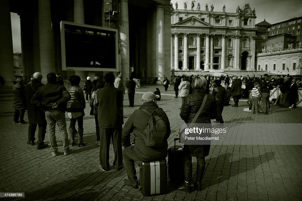 People sit in St Peter's Square as they wait for Pope Francis to give the Angelus blessing on February 23, 2014 in Vatican City, Vatican. Pope Francis created 19 new cardinals yesterday in a ceremony in St Peter's Basilica.