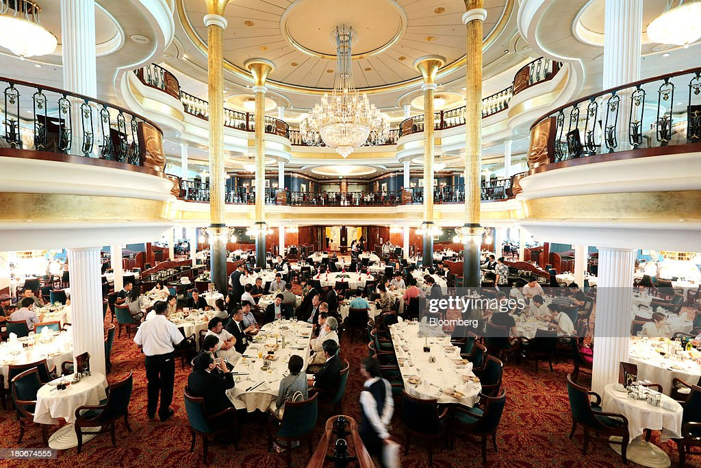 People sit in the 'Carmen' dining room aboard the Royal Caribbean Cruises Ltd.'s Voyager of the Seas, berthed at the Ohi wharf in Tokyo, Japan, on Saturday, Sept. 14, 2013. Royal Caribbean, the worlds second-largest cruise-line operator, doubled its dividend and will make directors stand for election every year. Photographer: Yuriko Nakao/Bloomberg via Getty Images