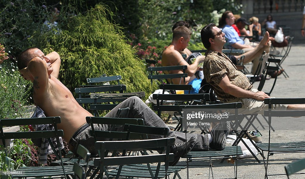People sit in the midday sun in Bryant Park July 7, 2010 in New York City. A blistering heat wave continued across the East Coast with temperatures approaching 100 degrees.