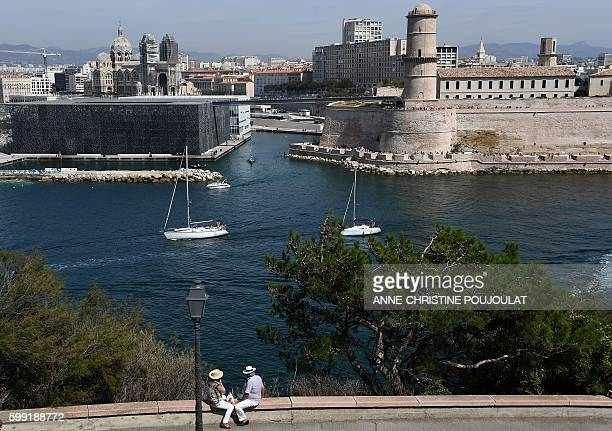 People sit in the Pharo garden in front of the Mucem museum and the Fort SaintJean on September 4 2016 in the harbour of Marseille / AFP /...