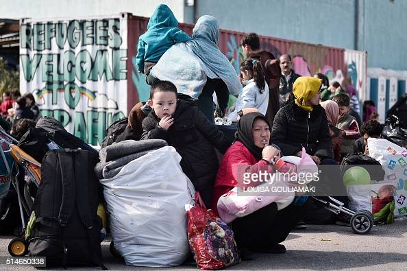 People sit in the port of Piraeus on March 10 as they wait with other migrants and refugees to be transferred to refugee camps in central Greece...