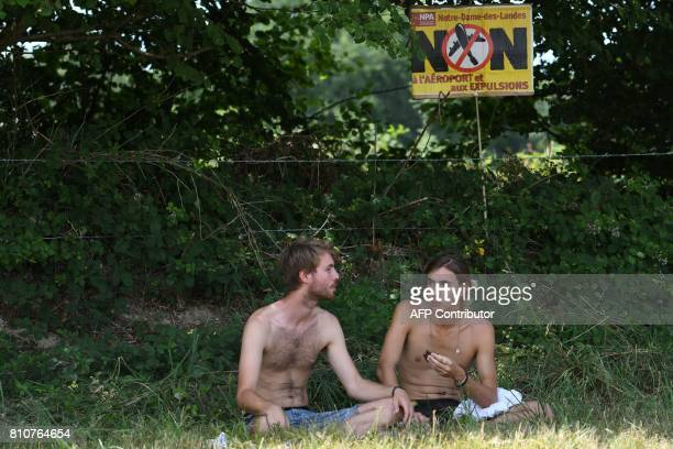 People sit in the shade under a sign reading 'Airport no No to airport and evictions' during a twoday meeting organised by opponents to a...