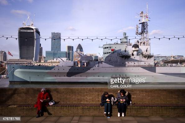 People sit in the sunshine with HMS Belfast on the River Thames in the background in central London on March 5 2014 Meteorological Spring started in...