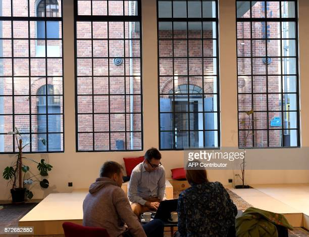 People sit inside The Art Factory in Lodz Poland on November 4 the former textile factory now offers coworking space exhibitions concerts and support...