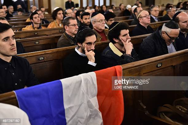 People sit near a French flag as they attend a ceremony for the victims of a series of deadly attacks at the Grande synagogue de la Victoire on...