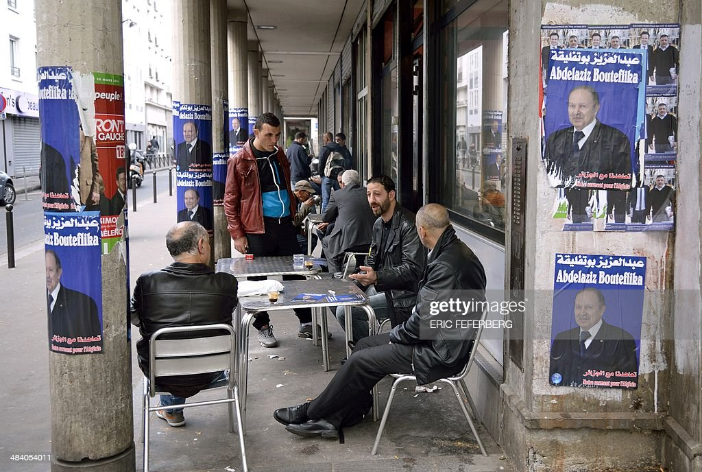 People sit near campaign posters for Algerian president Abdelaziz Bouteflika at a cafe terrasse in a street of the 'Goutte d'Or' district of Paris on April 11, 2014. Long held in suspicion in a largely state-controlled economy, Algerian businessmen are pouring cash into President Abdelaziz Bouteflika's re-election campaign, hoping to benefit from an expected fourth term for the incumbent. By law, candidates are supposed to spend no more than $764,000 (600,000 euros) on their campaign unless the election goes to a second-round runoff. But analysts say the legal limit is set impossibly low for a country which is Africa's largest by area, paving the way for effectively unrestricted spending by the candidates, with the incumbent leading the way. AFP PHOTO / ERIC FEFERBERG
