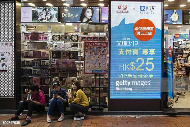 People sit next to an advertisement for Ant Financial Services Group's Alipay an affiliate of Alibaba Group Holding Ltd outside a Bonjour Holdings...