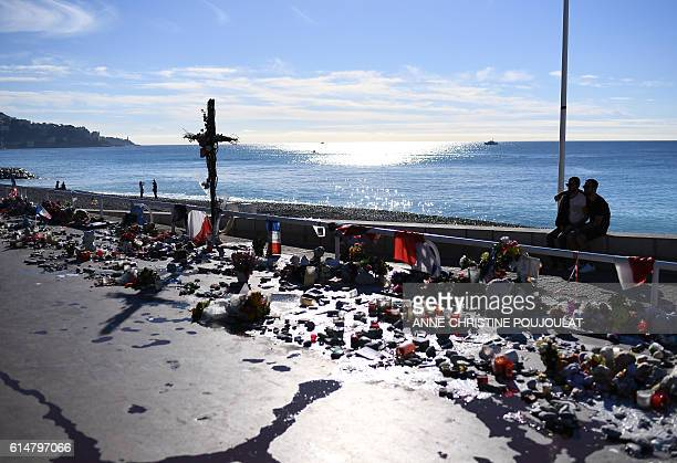 People sit next to candles flowers and flags placed in commemoration to victims at the Promenade des Anglais in Nice southeastern France on October...