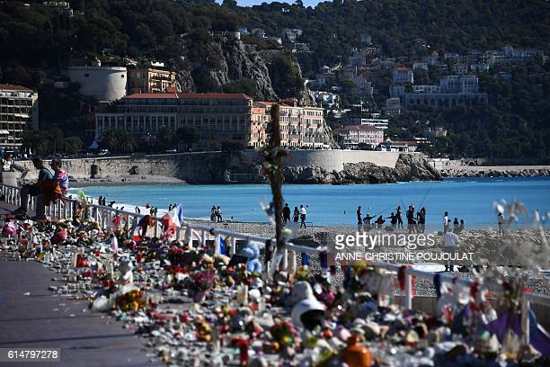 People sit next to candles flowers flags and various items placed in commemoration to victims at the Promenade des Anglais in Nice southeastern...
