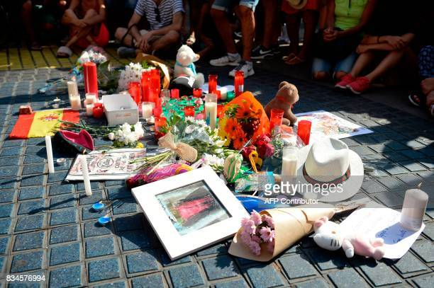 TOPSHOT People sit next to flowers messages stuffed toys and others items displayed on the Rambla boulevard on August 18 to pay tribute to the...