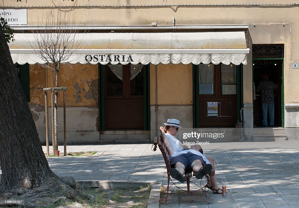 People sit on a bench in the shade in front of an Osteria on the Island of Murano on June 21, 2012 in Venice, Italy. An intense heatwave is sweeping across many regions in Italy, prompting the country's health ministry to issue a number of high level alerts.