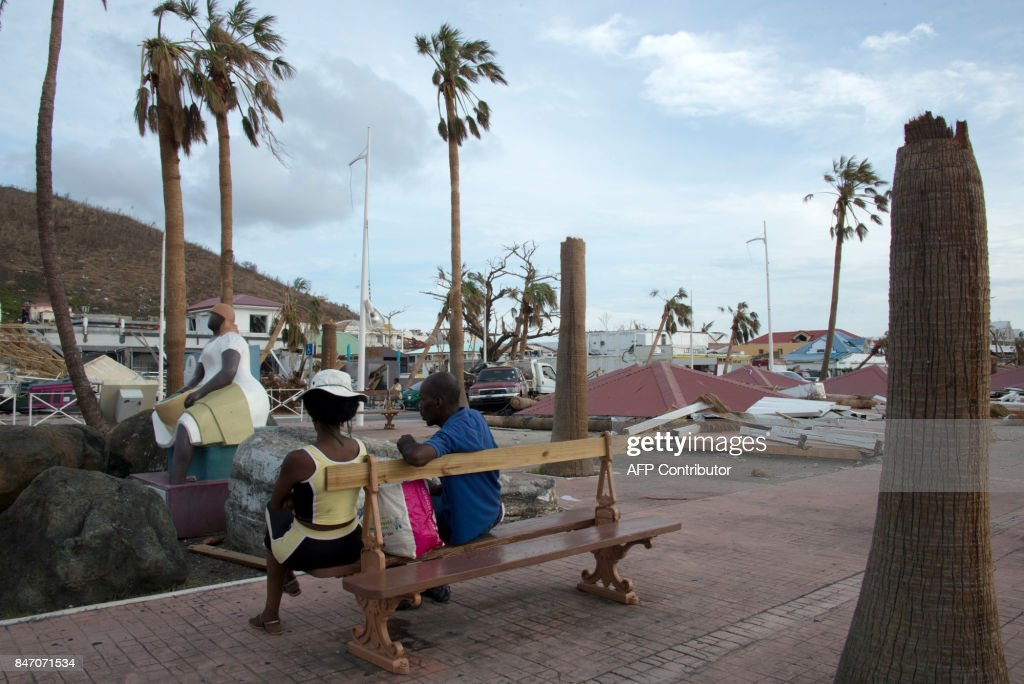 People sit on a bench near damages on September 14, 2017 in Marigot on the French Caribbean island of Saint Martin, after the island was hit by Hurricane Irma. The Category 4 hurricane, which struck in 1995, killed 19 people in St Martin, Antigua, Barbuda, St Barts and Anguilla and left tens of thousands homeless. Irma left 15 dead on both sides of St Martin. PHOTO / Helene Valenzuela