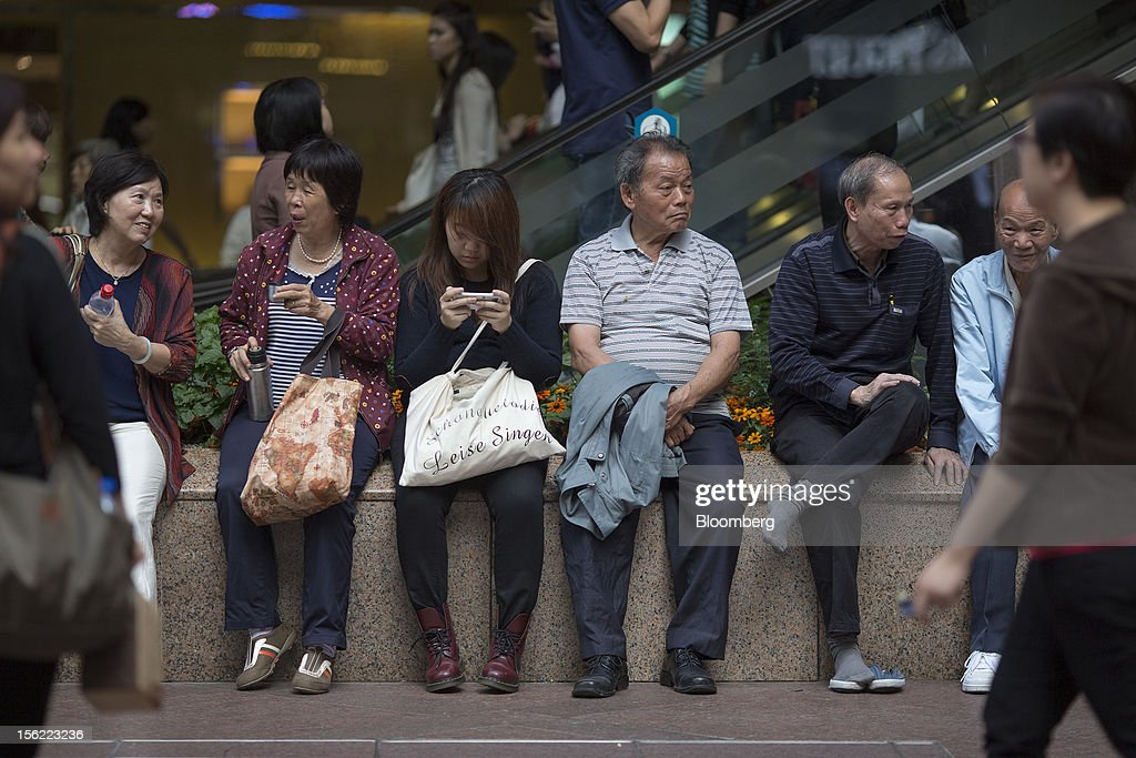 People sit on a bench outside Times Square shopping mall, operated by Wharf (Holdings) Ltd., in the Causeway Bay district of Hong Kong, China, on Friday, Nov. 9, 2012. Wharf (Holdings) Ltd. is controlled by the family of billionaire Chairman Peter Woo. Photographer: Jerome Favre/Bloomberg via Getty Images