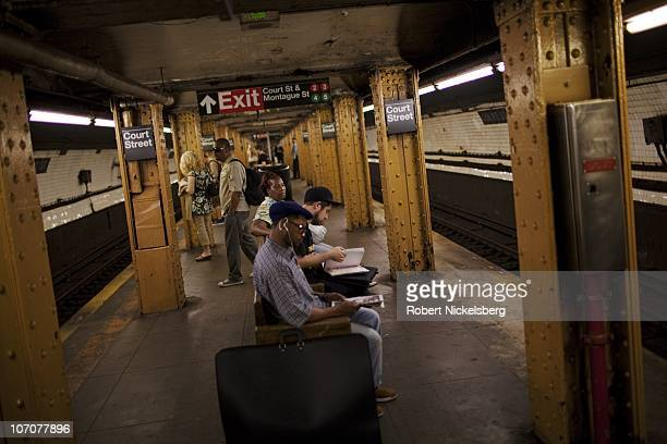 People sit on a bench waiting for the subway to arrive June 15 2010 in Brooklyn New York New York's Metropolitan Transit Authority recently voted to...