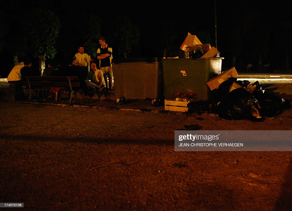 People sit on a bench where an open-air dance hall was hit by a violent storm which collapsed on the audience during the evening, injuring three people very seriously and 27 lightly, on July 28, 2013 in Joinville, Haute-Marne, eastern France. AFP PHOTO / JEAN-CHRISTOPHE VERHAEGEN
