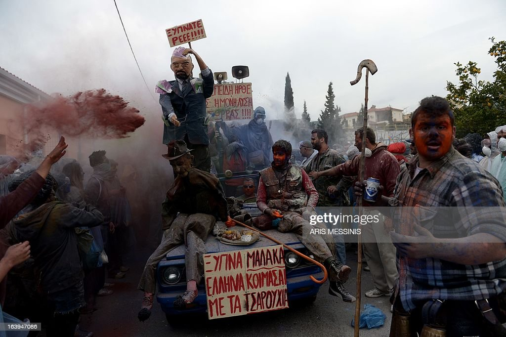 People sit on a car as they celebrate the annual custom of Flour War in Galaxidi, some 250kms south east of Athens on March 18, 2013. AFP PHOTO / ARIS MESSINIS