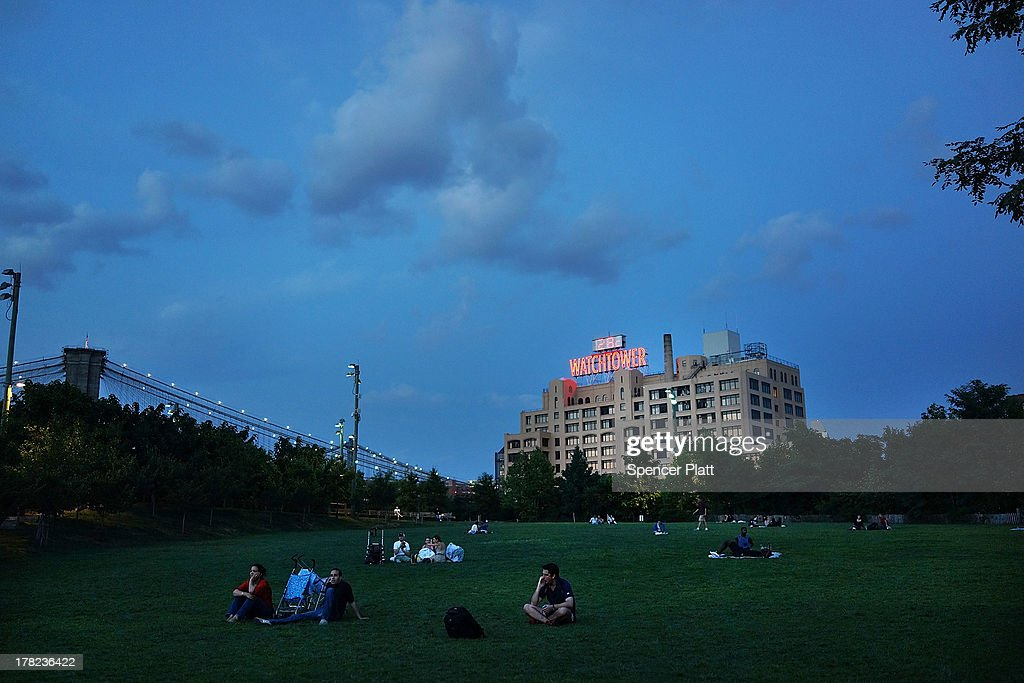 People sit on a lawn in the Brooklyn Bridge Park a newly designed outdoor space on the East River in Brooklyn August 27 2013 in New York CityThe park...