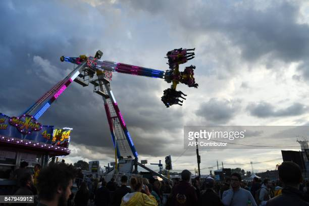 People sit on a ride during the 82nd edition of the annual 'Fete de l'humanite' music festival organized by French newspaper L'Humanite in La...