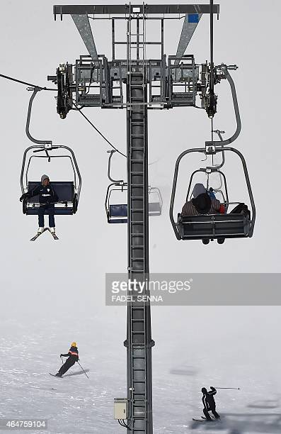 People sit on a ski lift at the Oukaimeden ski resort in the Atlas Mountains 30 kilometres from the popular tourist resort of Marrakesh on February...