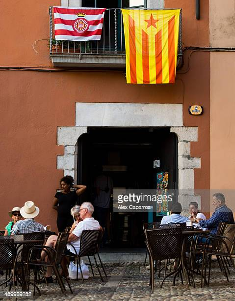 People sit on a terrace beneath proindependence and Girona FC football team flags on September 24 2015 in Girona Spain Over 5 million Catalans will...