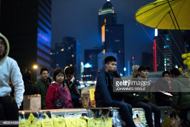 People sit on a wall as they listen to a speaker at the movement's main protest site in the Admiralty district of Hong Kong on December 6 2014 Joshua...