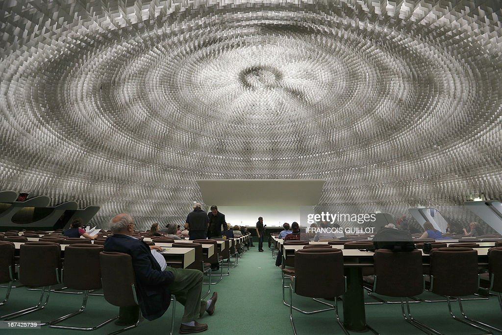 People sit on April 25, 2013 in the main conference room of the headquarters of the French Communist Party in Paris, a building designed by Brazilian architect Oscar Niemeyer.