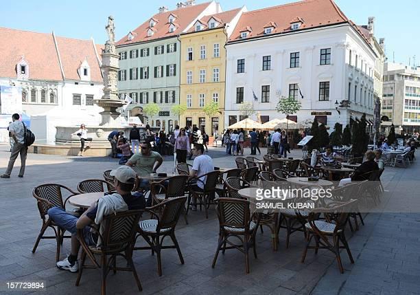 People sit on April 30 2010 at a cafe in the center of Bratislava AFP PHOTO / SAMUEL KUBANI