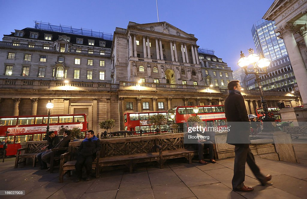 People sit on benches as London buses pass in front of the Bank of England (BOE), center, in London, U.K., on Wednesday, Jan. 9, 2013. Bank of England policy makers will probably refrain from adding further stimulus to the U.K. economy today as their new credit-boosting program shows early signs of success. Photographer: Chris Ratcliffe/Bloomberg via Getty Images