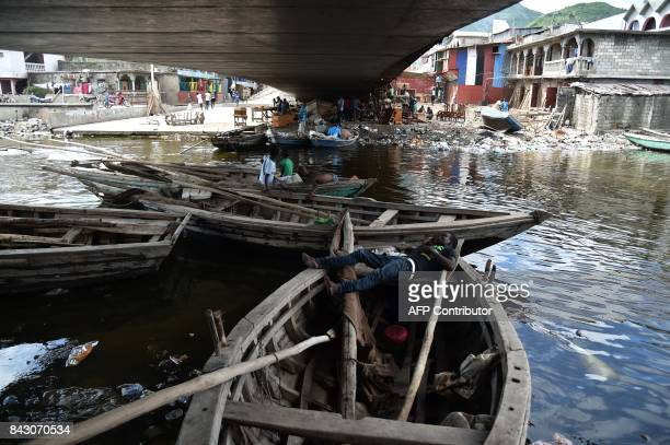 People sit on boats in Mapou River in Shadaa neighborhood in CapHaitien in the north of Haiti 240 km from PortauPrince ahead of Hurricane Irma on...