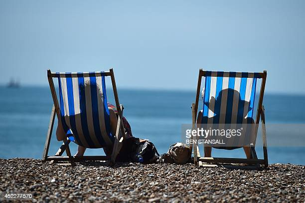 People sit on Brighton beach in Sussex southern England on July 17 2014 Britons were sent scampering for shade as the temperature soared to 291C the...