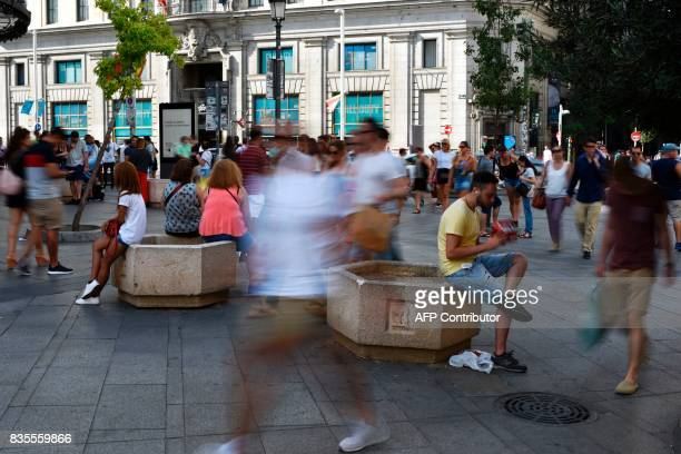People sit on concrete barriers displayed at the entrance of a pedestrian street near Gran Via in Madrid on August 19 two days after a van ploughed...