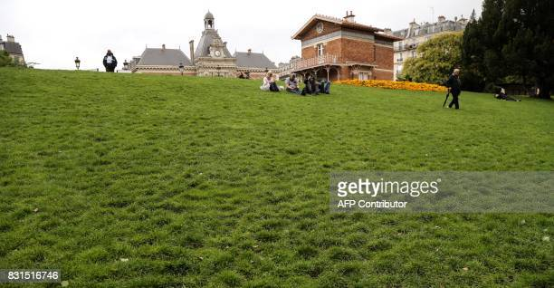 People sit on grass as the roof of Paris' 19th district hall is seen in the backround in the ButtesChaumont Park in Paris on August 12 2017 The...