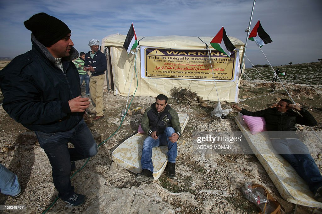 People sit on matresses in front of a tent that Palestinian activists set up in an 'outpost' named Bab al-Shams ('Gate of the Sun') between Jerusalem and the Jewish settlement of Maale Adumim in the Israeli-occupied West Bank, in an area where Israel has vowed to build new settler homes, on January 12, 2013. The Israeli occupation administration gave Palestinian activists an ultimatum to quit the protest camp in part of the West Bank, but hours after the deadline passed, there was no sign of any Israeli move to evict the protesters. AFP PHOTO/ABBAS MOMANI