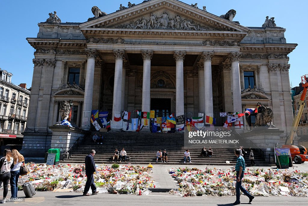 People sit on steps in front of the makeshift memorial for victims of the March 22, 2016 terror attacks at the Place de la Bourse (Beursplein) in Brussels on May 5, 2016, during a sunny day. / AFP / Belga / NICOLAS MAETERLINCK / Belgium OUT