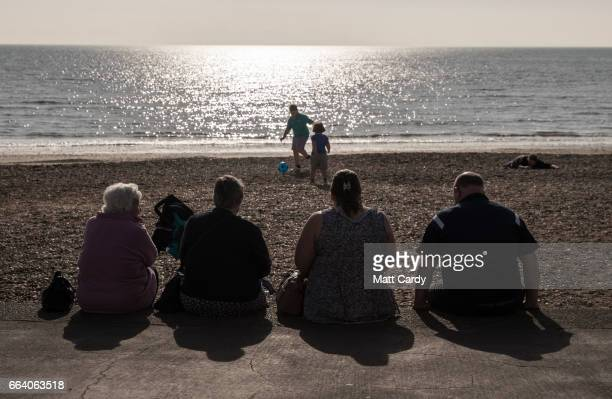 People sit on the beach at Weymouth as the resort prepares for the start of the holiday season on April 3 2017 in Dorset England With the Pound still...