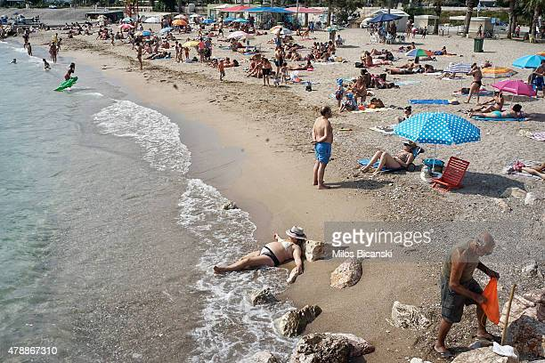 People sit on the beach near the water on June 28 2015 in Athens Greece Greece is anxiously awaiting a decision by the European Central Bank on...